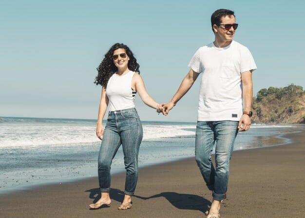 couple-walking-barefoot-sandy-beach