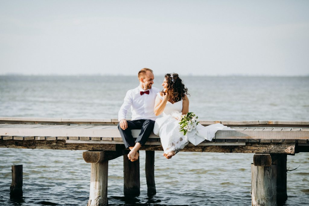 bride-and-groom-sitting-on-wooden-dock-3860080